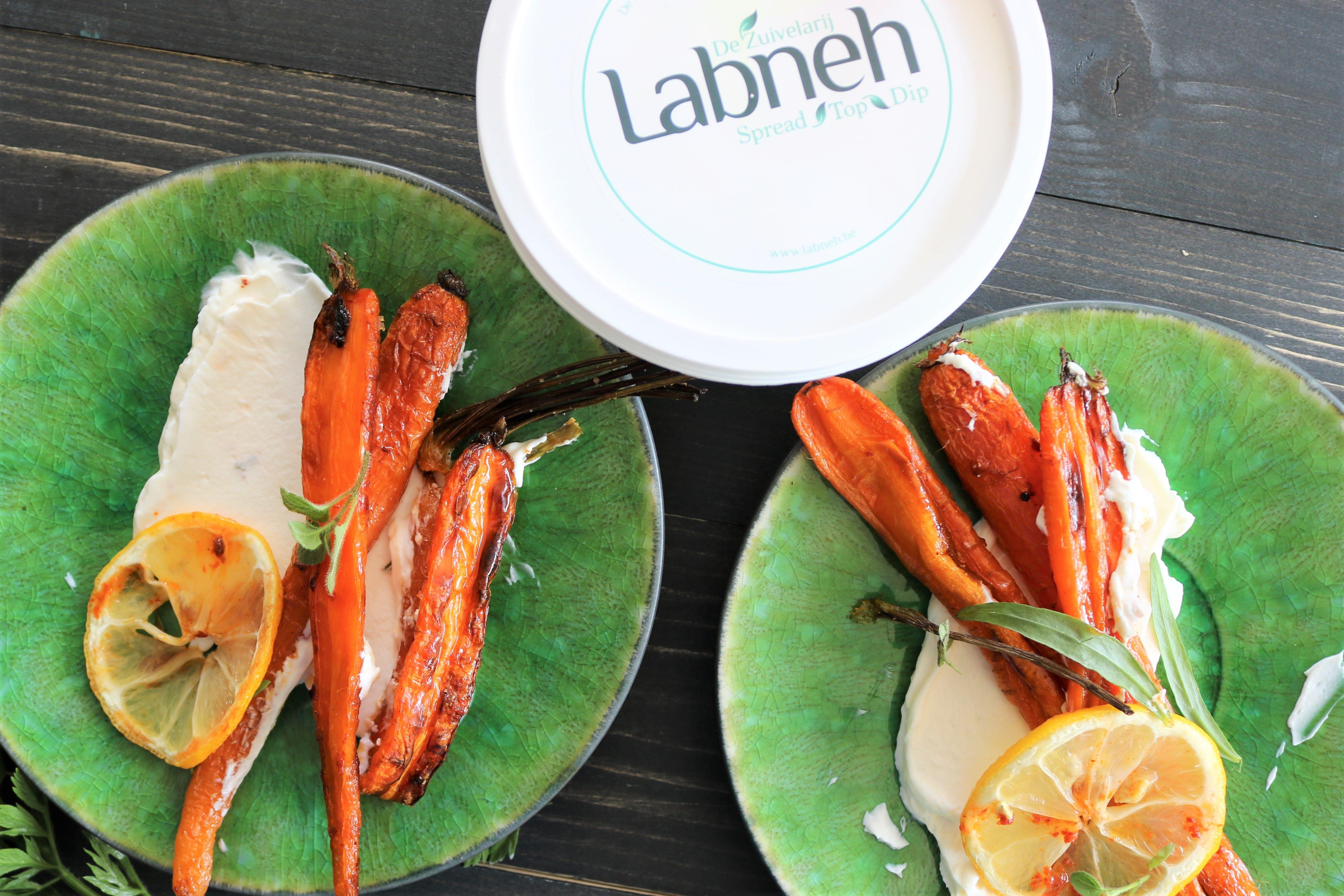 Geroosterde wortelen op een groen klein bord met labneh en citroen.